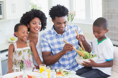 Happy family sitting down to dinner together Stock Photography