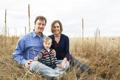 Happy family sitting in field. Happy caucasian family sitting in field together looking at camera Stock Image