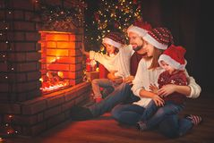 Happy family sitting by fireplace on Christmas Eve Stock Images
