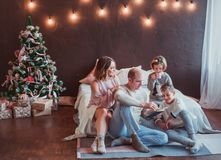 Happy family sitting on the floor by the bed in the new year interior. Dad is reading a book. Children laugh. Cozy room royalty free stock photo