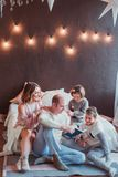 Happy family sitting on the floor by the bed in the new year interior. Dad is reading a book. Children laugh. Cozy room stock photography
