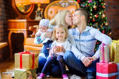 Happy family sitting on the floor near the Christmas tree stock photography