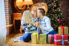 Happy family sitting on the floor near the Christmas tree royalty free stock photo