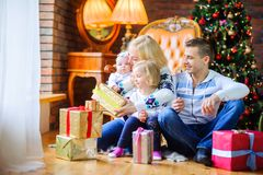 Happy family sitting on the floor near the Christmas tree Stock Images