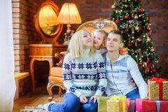 happy family sitting on the floor near the festive Christmas tree, daughter holding a small gift hugging parents, positive stock images