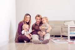 Happy family sitting on floor with their little babies Family spending time at home with their son and daughter.  stock photos