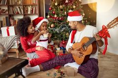 Family sitting on floor together and listening guitar songs at home on Christmas holiday. Happy family sitting on floor together and listening guitar songs at royalty free stock photos