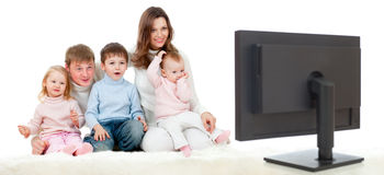 Happy family sitting on floor and watching TV Stock Images