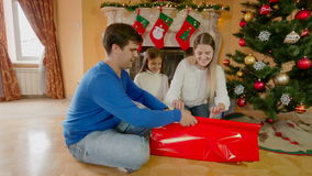 Happy family sitting on floor and wrapping Christmas presents in paper and decorating with ribbons. Family sitting on floor and wrapping Christmas presents in stock footage