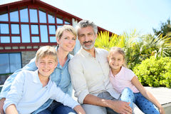 Happy family sitting in font of their home Royalty Free Stock Photography
