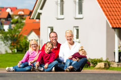 Happy family sitting in front of home Royalty Free Stock Photos