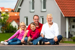 Happy family sitting in front of home Stock Photos