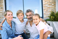 Happy family sitting in front of the house Stock Photo
