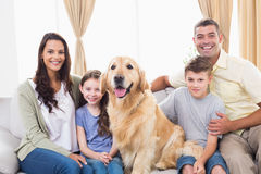 Happy family sitting with Golden Retriever on sofa Stock Image