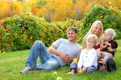 Happy Family Sitting in the Grass Eating Apples at Royalty Free Stock Photography