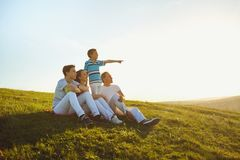 Happy family sitting in nature at sunset in the sun. Happy family sitting on the grass in nature at sunset in the sun stock photography