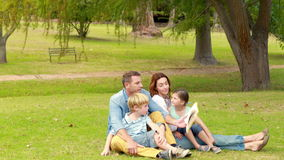 Happy family sitting on grass and reading book stock footage