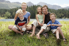 Happy Family Sitting On Grassy Field Stock Photos