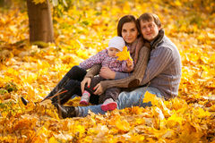 Happy family sitting on leaves at autumn park Royalty Free Stock Photography