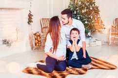 Happy family sitting in the living room, behind the decorated Christmas tree, the light give a cozy atmosphere. New Year and xmas theme stock photo