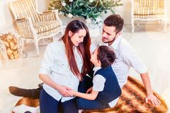 Happy family sitting in the living room, behind the decorated Christmas tree, the light give a cozy atmosphere. New Year and xmas theme royalty free stock photo