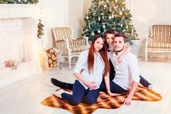 Happy family sitting in the living room, behind the decorated Christmas tree, the light give a cozy atmosphere. New Year and xmas theme royalty free stock photos