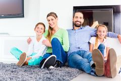 Family sitting at living room floor fireplace Stock Photo