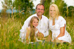 Happy family sitting in meadow Royalty Free Stock Photography
