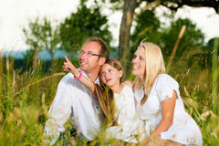 Happy family sitting in meadow Stock Photos