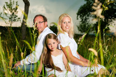 Happy family sitting in meadow Stock Image