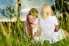 Happy family sitting in meadow Stock Images