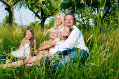 Happy family sitting in meadow Royalty Free Stock Images