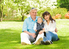 Happy family sitting on a meadow Stock Photos