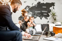 Woman and baby boy with travel agent at the office. Happy family sitting with men agent at the travel agency office with beautiful map on the background choosing Stock Photos