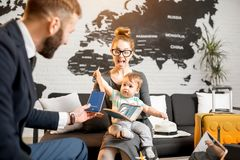 Woman and baby boy with travel agent at the office. Happy family sitting with men agent at the travel agency office with beautiful map on the background Royalty Free Stock Images
