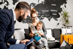 Woman and baby boy with travel agent at the office. Happy family sitting with men agent at the travel agency office with beautiful map on the background Stock Photos