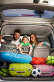 Happy family sitting in a minivan full of luggage Royalty Free Stock Photos