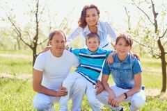Happy family sitting on nature in spring, summer. Mother, father and sons in the field Stock Photo