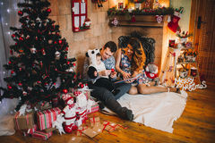 Happy Family Sitting Near Christmas Tree. Happy family at Christmas and New Year with gifts around the Christmas tree read book. in Christmas Stock Photo