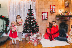 Happy Family Sitting Near Christmas Tree.  in red Stock Photo