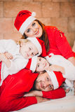 Happy Family Sitting Near Christmas Tree.  in red Royalty Free Stock Photography