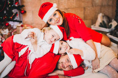 Happy Family Sitting Near Christmas Tree.  in red Royalty Free Stock Photo