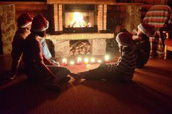 Happy family sitting near fireplace and celebrating Christmas and New Year, parents and children in Santa hats. Happy family sitting near fireplace at home and royalty free stock image