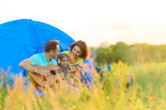 Happy family sitting near tent Stock Images