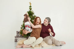 Happy family sitting at the new-year tree on white studio Royalty Free Stock Images