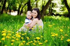 Happy family sitting outside in a field of dandelion flowers Royalty Free Stock Photography