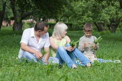 Happy family sitting in park Stock Photos