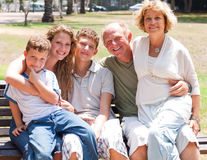 Happy family sitting on park bench Stock Photography