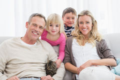 Happy family sitting with pet kitten together Stock Images