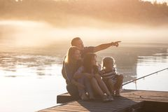 Happy family  sitting on the pier Royalty Free Stock Images